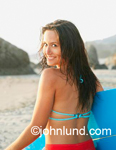 Photo of a woman surfer with her surfboard looking back over her shoulder at the camera. She is happy and smiling.  She has long brown hair and a blue surfboard. A lifestyle stock photo.